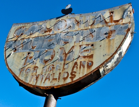 "The sign reads, ""Colonial Nursing Home for Aged and Invalids."" The sign has outlasted the nursing home."