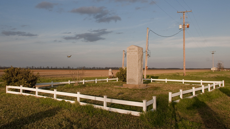 A quarter mile or so north of the smoke stack, is a memorial to the Jerome Relocation Camp internees. Being in the Delta, in a farm area, no space is wasted. An irrigation pump sits close by. In the background, you can see a cropduster winging his way home.