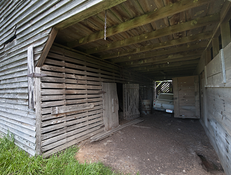 "You are looking at the livestock side of the barn, above. There were two ""rooms."" The door to the second ""room"" is just to the left of the car. The stairs to the second floor are also in that room. It is presumed that one side was for beasts of burdern, horses and mules. And the other side was for cattle."