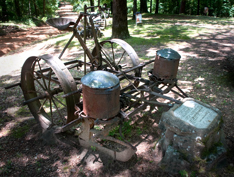 """A large number antique farm implements place around the grounds are visible evidence of the agrarian nature of the areas economy in the 19th and early 20th centuries. Plaques at every piece of equipment give evidence of  it use. This horse-drawn planter is a good example. The planter was donated to the cemetery collection in memory of  Tate """"Uncle Bud"""" McGehee """"Miss Vaughn"""" McGehee. Family member Edgar Colvin installed the planter at the cemetery, The plaque information, typical of the collection reveals a story. The planter was bought by Mr. McGehee in 1920. He always said, """" ... this planter is so accurate that if it drops two seeds in a hill, it will reach back and pick up one of them."""""""