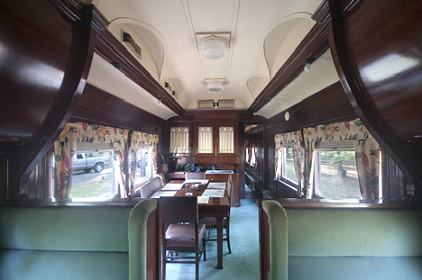 The main parlor from closer to the front of the car. Note the overhead storage and richly upholstered seats.