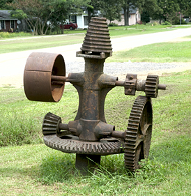 This piece of machinery, the use of which remains a mystery, adorns the side yard of the old building above.