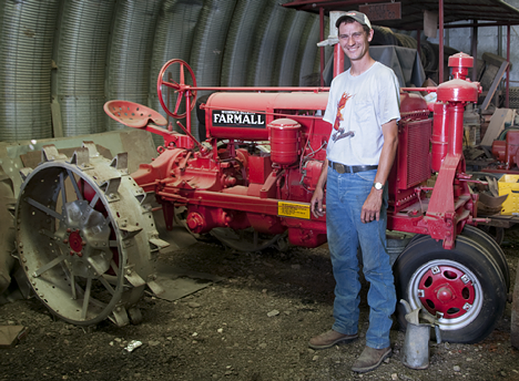 Mason Sickel smiles beside his showroom new antique Farmall tractor. It is restored to perfection and is typical of the Sickel collection.
