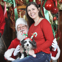 Girl and dog in Santa's lap