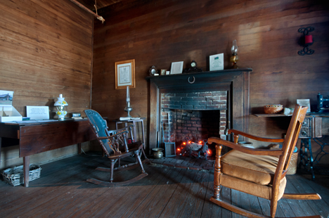 Old living room with large brick fire place.