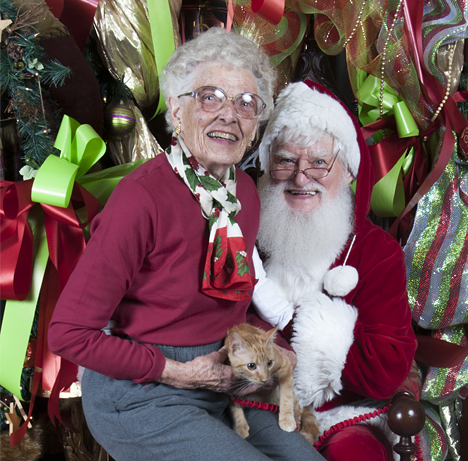 Grandmother and cat in Santa's lap