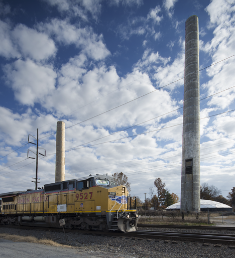 Train passing smoke stacks left from old Arkansas Power and Light Co, generating plant demolition.