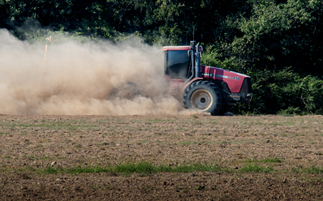 Tractor pulling land leveler in dust