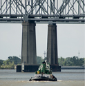 tow boat and new orleans bridge