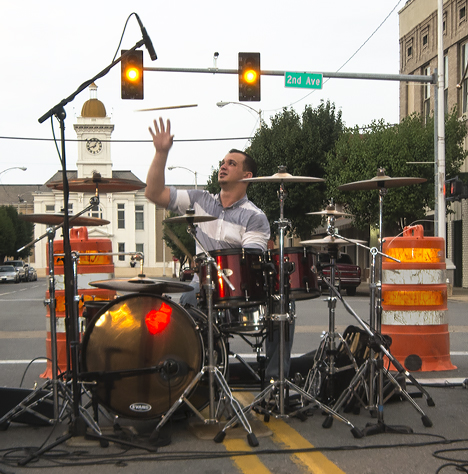 "Drummer Tim Dickerson with the Brian Austin band offers some drumstick gymnastics as additional entertainment to his rhythmic skills as a percussionist. The band is playing at the August 2, 2013 ""Music on Main"" concert on Main Street in Pine Bluff, Arkansas."
