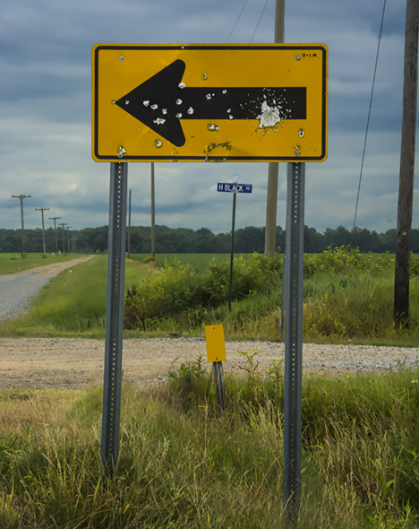 Road sign with gunshot strikes
