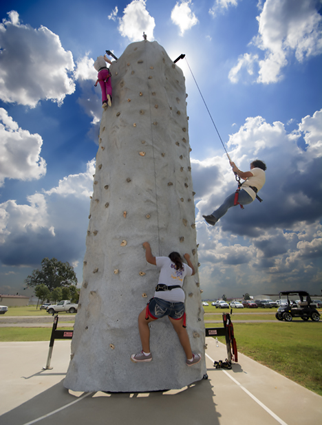 three kids on rock climbing obstacle