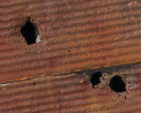 Shot gun holes in tin building