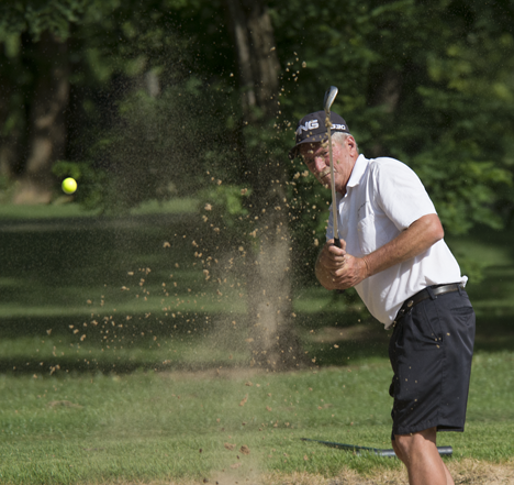 golfer blasting from sand trap