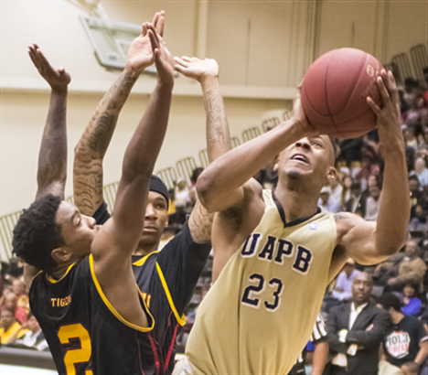 UAPB player shoots basketball against two defenders