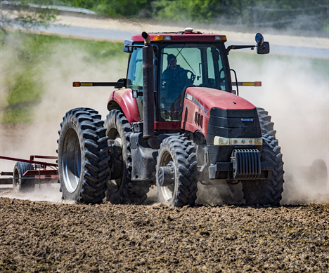 Large tractor pulling a scratcher through a dry field